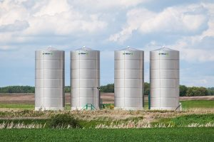 Four liquid bins lined up in a field